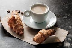 在一个杯子的早晨浓咖啡在一张桌上用在前面的新月形面包 免版税库存图片