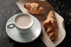 在一个杯子的早晨浓咖啡在一张桌上用新月形面包 免版税库存照片