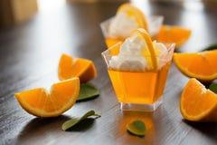 在一个杯子的橙色果冻有打好的在bl切的奶油和桔子的 免版税库存照片