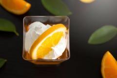 在一个杯子的橙色果冻有打好的在bl切的奶油和桔子的 免版税图库摄影