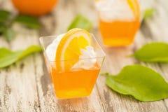 在一个杯子的橙色果冻有打好的在bl切的奶油和桔子的 免版税库存图片