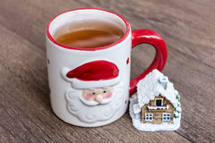 在一个杯子的热的冬天茶有圣诞节装饰房子的 库存照片