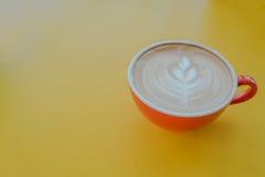 在一个杯子的热的艺术拿铁咖啡在木桌上 免版税库存照片