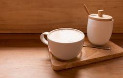 在一个杯子的热的艺术拿铁咖啡在木桌和咖啡店上 库存照片