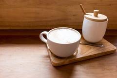 在一个杯子的热的艺术拿铁咖啡在木桌和咖啡店上 库存图片