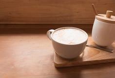 在一个杯子的热的艺术拿铁咖啡在木桌和咖啡店上 免版税库存图片