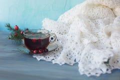 在一个杯子的茶在一张灰色桌上用与圣诞节tre的红色莓果 库存照片