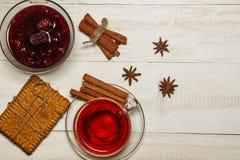 在一个杯子的茶用山莓果酱,曲奇饼,新月形面包,桂香,茴香,焦糖黏附 在一张白色木桌上 圣诞节composit 免版税库存照片