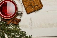 在一个杯子的茶用山莓果酱,曲奇饼,新月形面包,桂香,茴香,焦糖黏附 在一张白色木桌上 圣诞节composit 库存图片