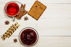 在一个杯子的茶用山莓果酱,曲奇饼,新月形面包,桂香,茴香,焦糖黏附 在一张白色木桌上 圣诞节composit 免版税图库摄影