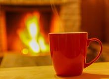 在一个杯子的茶,在舒适壁炉背景 免版税库存照片