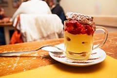 在一个杯子的草莓奶油甜点在木桌上 免版税库存图片
