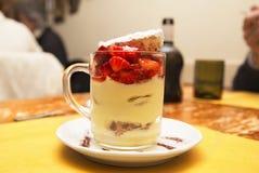 在一个杯子的草莓奶油甜点在木桌上 库存图片