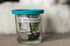 在一个杯子的退休计划资金有一个绿色盒盖的 免版税库存照片