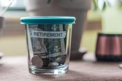 在一个杯子的退休计划资金有一个绿色盒盖的 库存图片