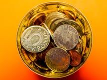 在一个杯子的金黄铜和银币有橙色背景 免版税库存图片