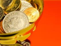 在一个杯子的金黄铜和银币有橙色背景 免版税图库摄影
