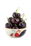 在一个杯子的黑樱桃在白色背景 免版税库存图片