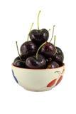 在一个杯子的黑樱桃在白色背景 免版税图库摄影
