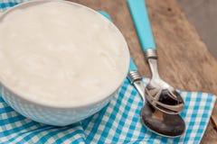 在一个杯子酸奶,在一把匙子的一块蓝色毛巾,在木后面 库存图片