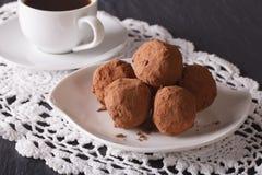 在一个板材和咖啡特写镜头的块菌状巧克力在桌上 库存图片