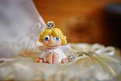 在一个枕头的一点玩具天使婚戒的 库存照片