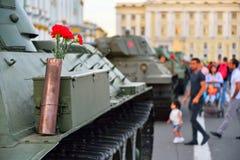 在一个枪弹药筒的红色康乃馨在一辆重的苏联坦克KV-1 库存照片