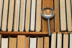 在一个架子的放大镜与书 库存图片