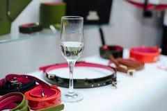 在一个架子的时髦的女人` s皮带与一杯香槟 皮革物品销售  免版税库存图片