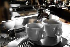 在一个柜台的意大利煮浓咖啡器在分与新近地煮的咖啡的餐馆入两个小杯子 库存照片
