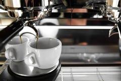 在一个柜台的意大利煮浓咖啡器在分与新近地煮的咖啡的餐馆入两个小杯子 免版税库存照片
