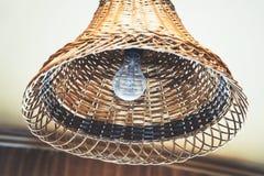 在一个柳条灯罩的电灯泡 免版税库存照片