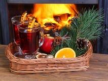 在一个柳条盘子的被仔细考虑的酒在壁炉背景  免版税库存照片