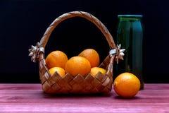 在一个柳条筐和一个绿色瓶的蜜桔在一个木选项 库存照片