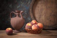 在一个柳条筐和她的投手的新鲜的桃子 免版税库存图片