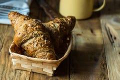 在一个柳条筐和搪瓷的整个五谷新月形面包在木桌上的背景中抢劫 库存图片