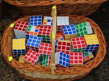 在一个柳条筐堆积的许多Rubik立方体 免版税库存图片