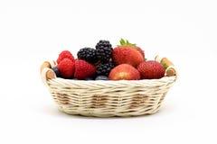 在一个柳条筐的夏天莓果在白色背景 图库摄影