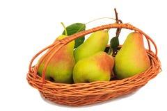 在一个柳条筐的大成熟梨在白色背景。 库存图片