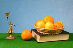 在一个柳条筐的柑桔在bronse小雕象旁边的一本书 图库摄影