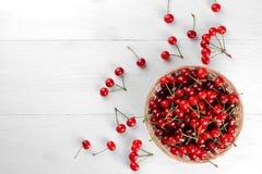 在一个柳条筐的被磨碎的成熟,红色,新鲜的樱桃在白色木背景 顶视图 库存图片