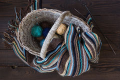 在一个柳条筐的被编织的羊毛围巾和毛线球在木头 免版税图库摄影