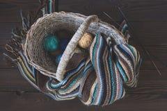 在一个柳条筐的被编织的羊毛围巾和毛线球在木头 免版税库存图片