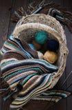 在一个柳条筐的被编织的羊毛围巾和毛线球在木头 图库摄影