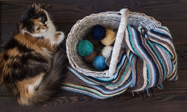 在一个柳条筐的被编织的羊毛围巾和毛线球在木头 免版税库存照片