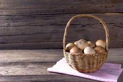 在一个柳条筐的鸡蛋在木桌上 库存照片