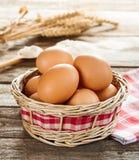在一个柳条筐的鸡蛋在葡萄酒木头桌上 库存图片