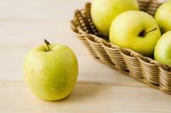 在一个柳条筐的黄色湿新鲜的苹果 免版税图库摄影
