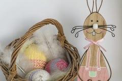 在一个柳条筐附近的一只木复活节兔子与三钩编了编织物在明亮的背景前面的鸡蛋 图库摄影