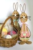 在一个柳条筐附近的两只木复活节兔子与三钩编了编织物在明亮的背景前面的鸡蛋 库存照片